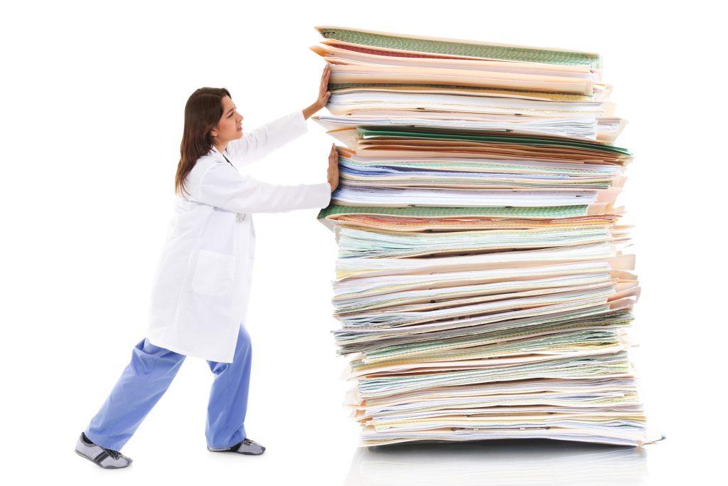 doctor pushing paperwork pile