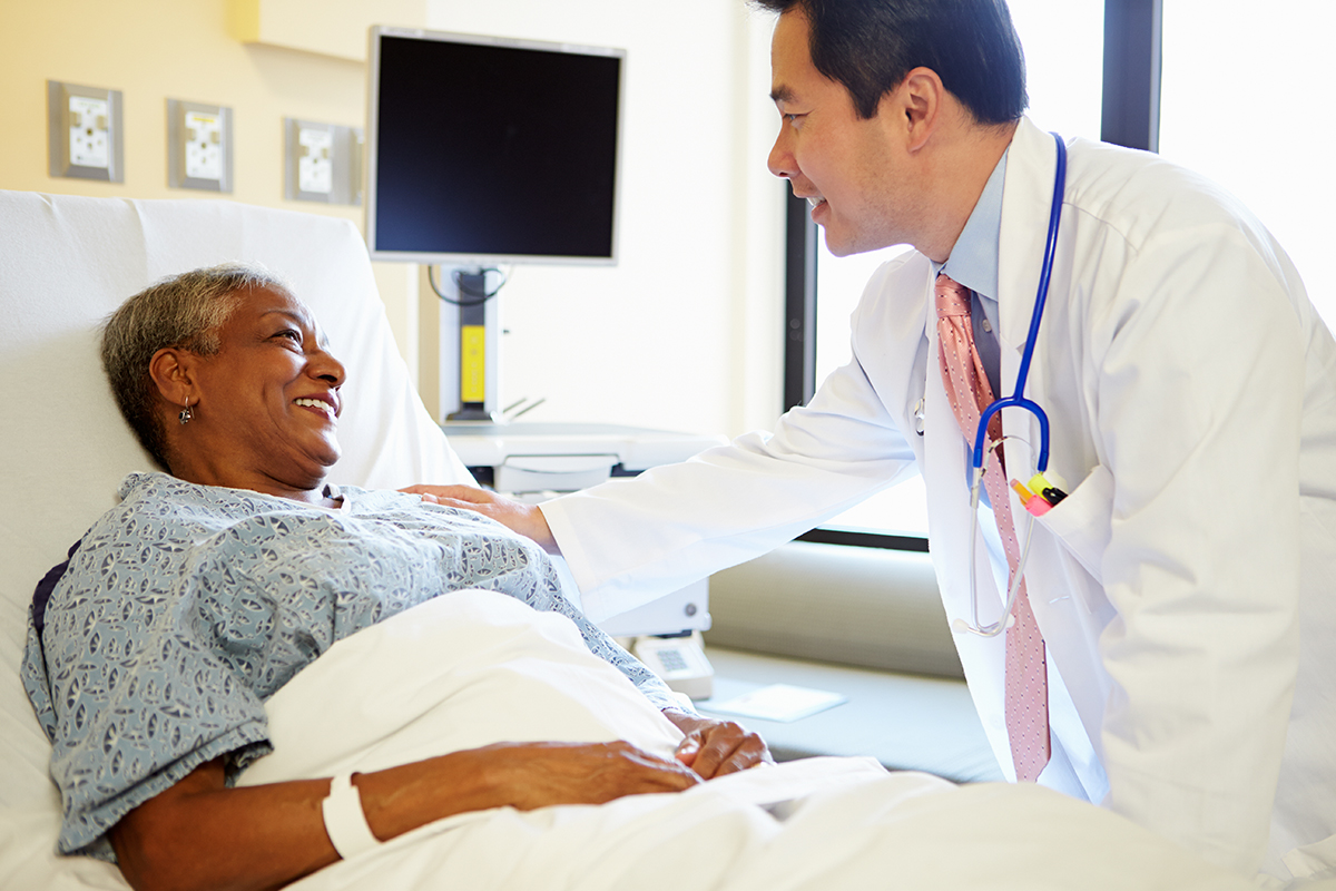 Doctor talking with patient in hospital bed